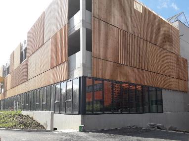 Extension d'un bâtiment avec murs rideaux et stores extérieurs